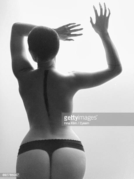 Rear View Of Tattooed Naked Woman Standing Against White Background