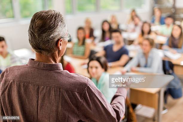 Rear view of teacher giving a lecture in the classroom.