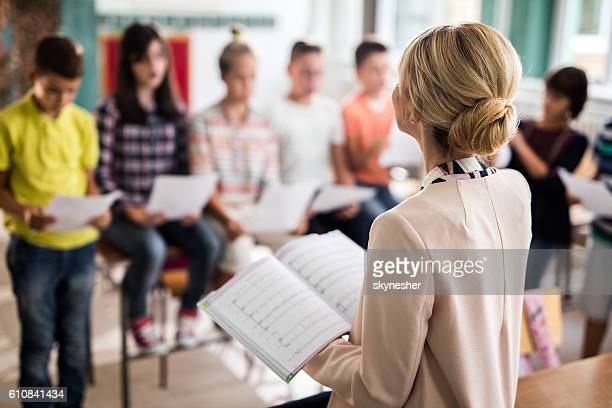 Rear view of teacher singing with children in the classroom.