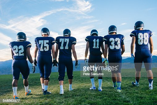 Rear view of teenage and young adult american football team in a row