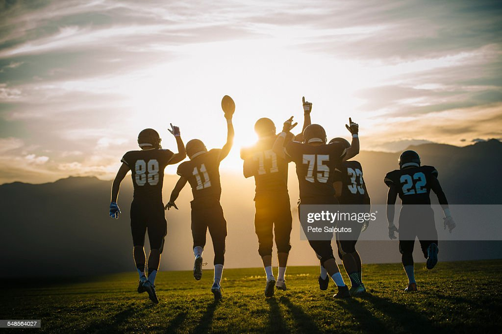 Rear view of teenage and young male american football team celebrating at sunset