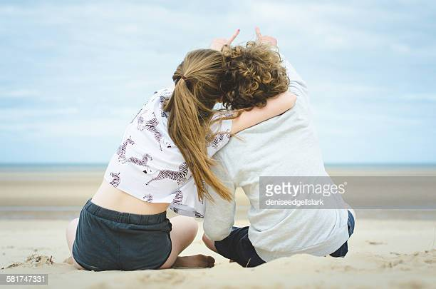Rear view of teenage boy and girl sitting on beach pointing at sky