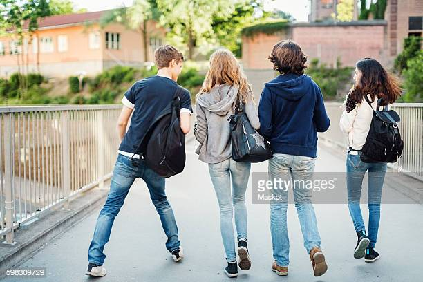 Rear view of teenagers walking on bridge in city