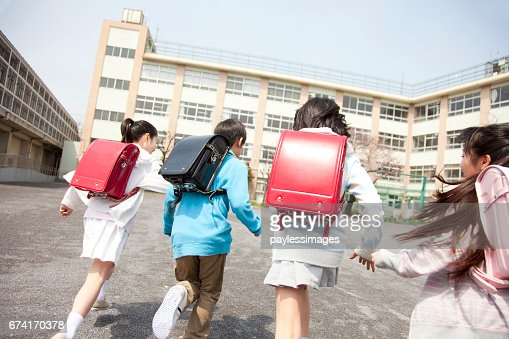 Rear view of the elementary school students go to school four : Stock Photo