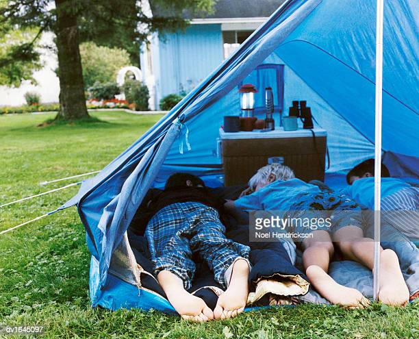 Rear View of Three Boys Lying Side by Side in a Tent in Their Garden