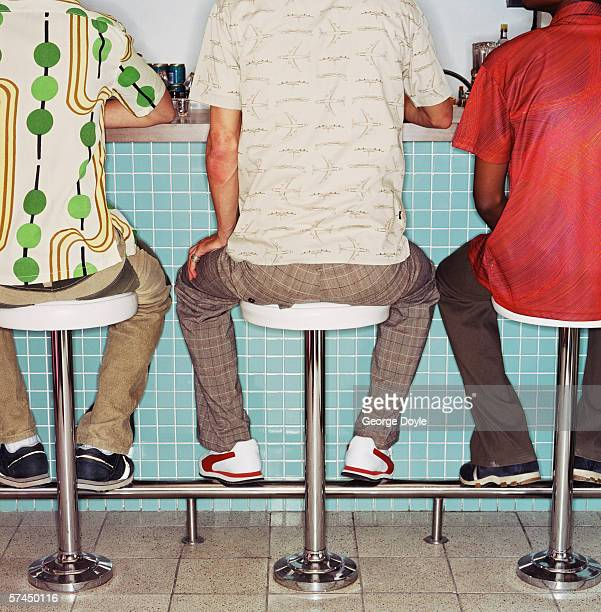 Rear view of three people sitting on bar stools