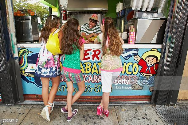 Rear view of three teenage girls talking to a bartender in a juice bar