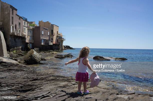Rear View Of Toddler Girl Holding Cap While Standing At Beach Against Sky