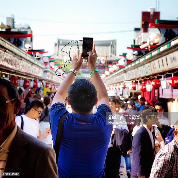 Vista posteriore del turista fotografare di Asakusa con telefono cellulare