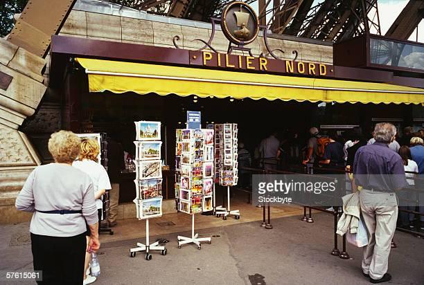 Rear view of tourists outside a souvenir shop