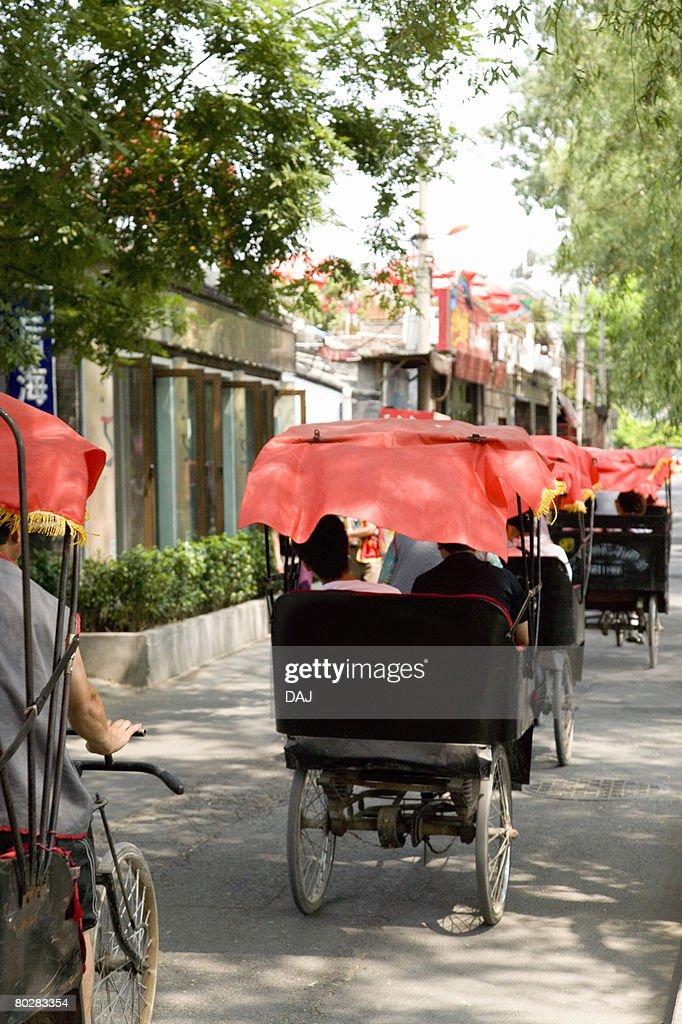 Rear view of tourists sitting in Chinese rickshaw, China, Beijing, Hutong