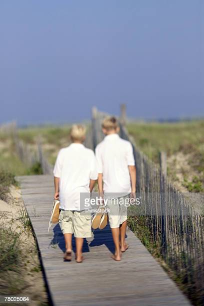 Rear view of two boys walking on a boardwalk towards the beach with their shoes in their hands