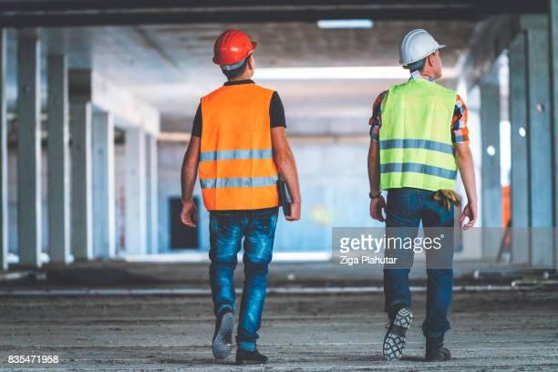 工事現場でヘルメットを着て白人の大人 2 人の後姿