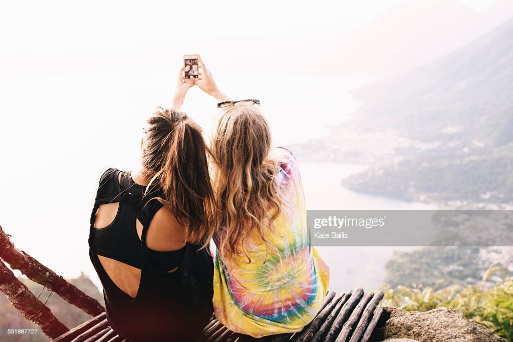 Rear view of two female friends taking smartphone selfie at Lake Atitlan, Guatemala