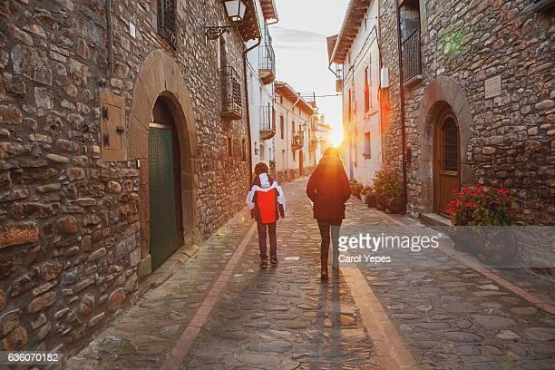 rear view of two kids walking in a village in pyrinees.Huesca
