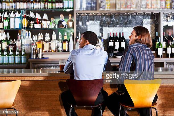 Rear view of two men at bar