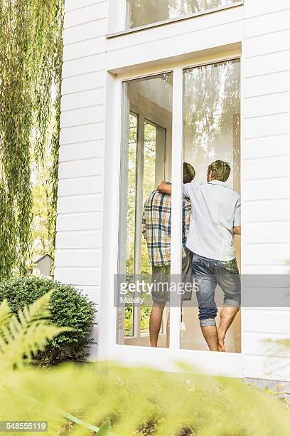 Rear view of two men at house window