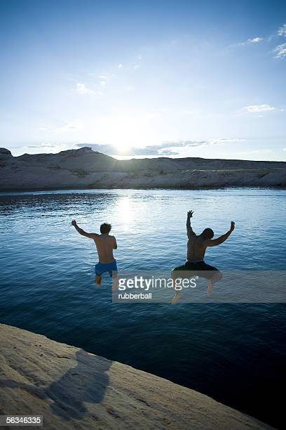 Rear view of two men jumping into a lake