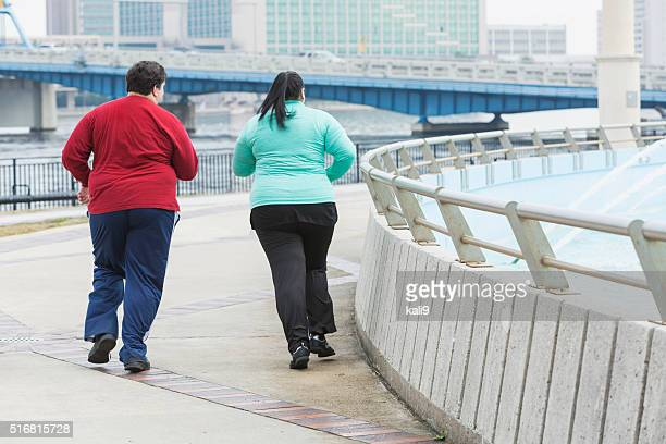 Rear view of two overweight people jogging