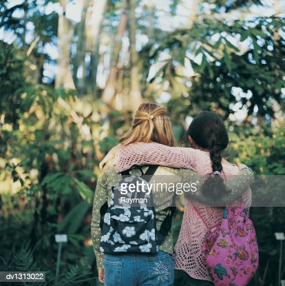 Rear View of Two Primary School Girls With their Arms Around Each Other on a Field Trip in a Botanical Garden
