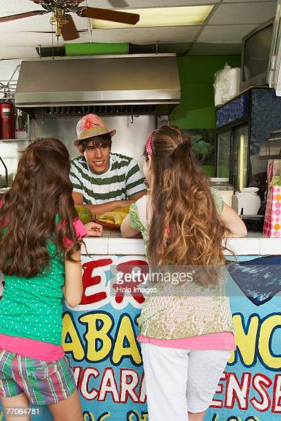 Rear view of two teenage girls talking to a bartender in a juice bar