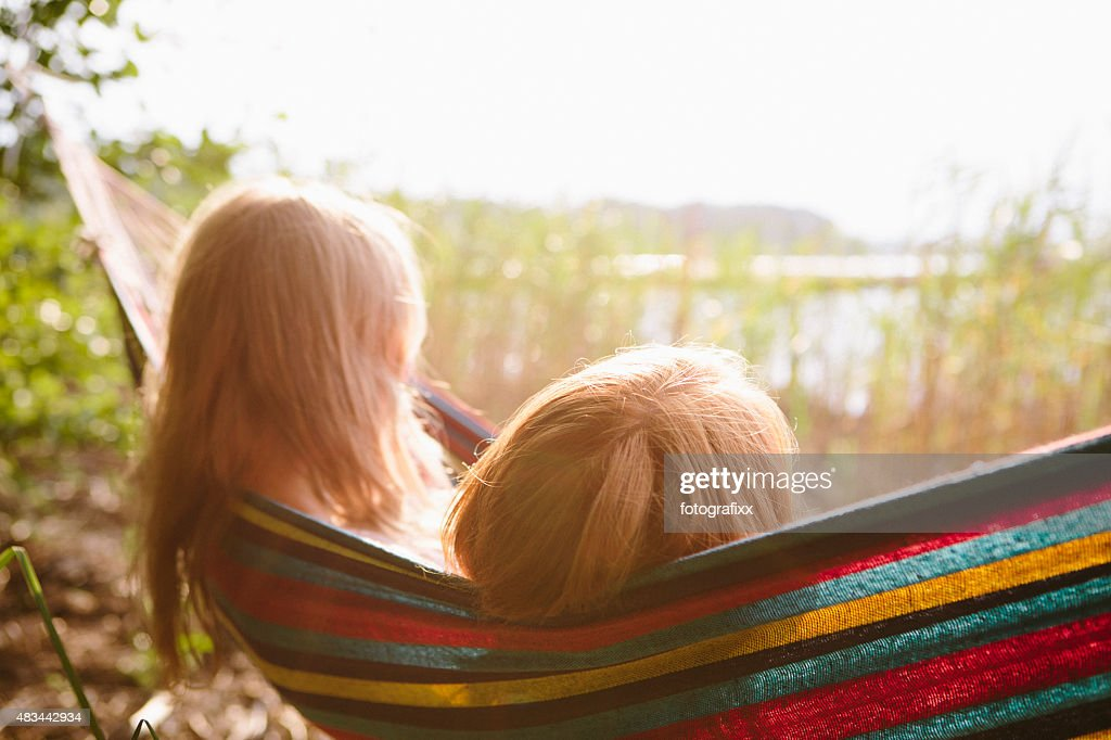 rear view of two women relax in hammock with backlit