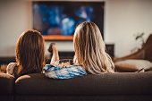Back view of female friends watching TV on sofa at home.
