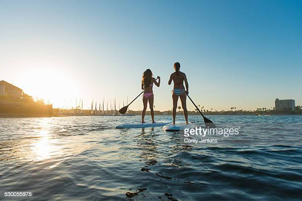 Rear view of two women stand up paddleboarding, Mission Bay, San Diego, California, USA