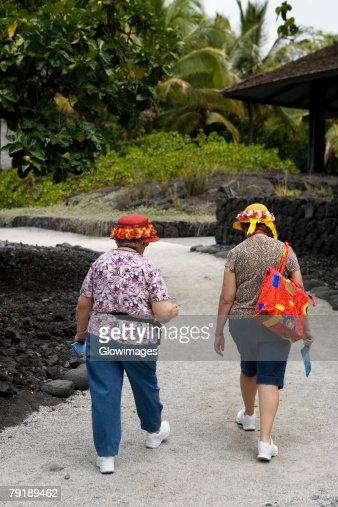 Rear view of two women walking on a walkway, Puuhonua O Honaunau National Historical Park, Kona Coast, Big Island, Hawaii Islands, USA : Foto de stock