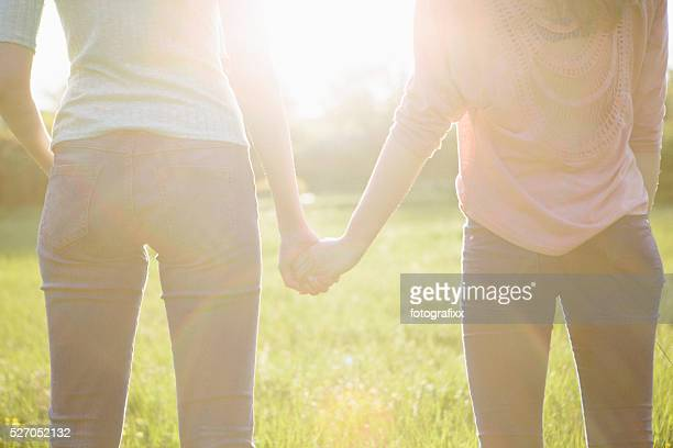 rear view of two young women holding hands, backlit