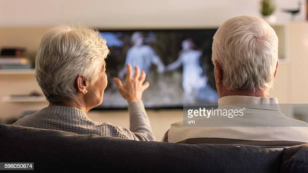 Rear view of unrecognizable senior couple looking television