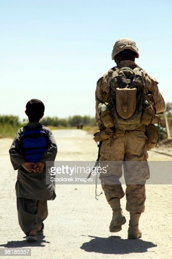 Rear view of U.S. Marine walking through Nawa bazaar with an Afghan boy in Afghanistan. : Foto de stock