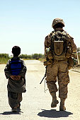 September 8, 2009 - U.S. Marine patrols through the Nawa bazaar with an Afghan boy in the Nawa district of Helmand province, Afghanistan.