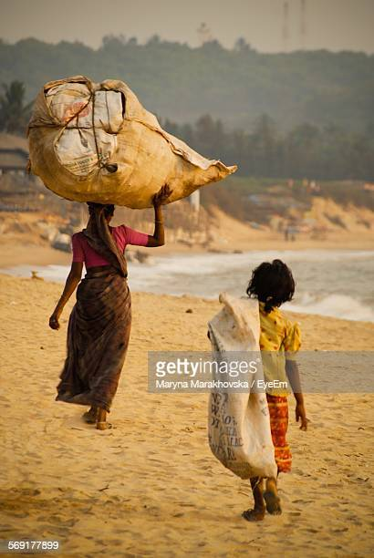 Rear view of woman and girl carrying burlap sacks