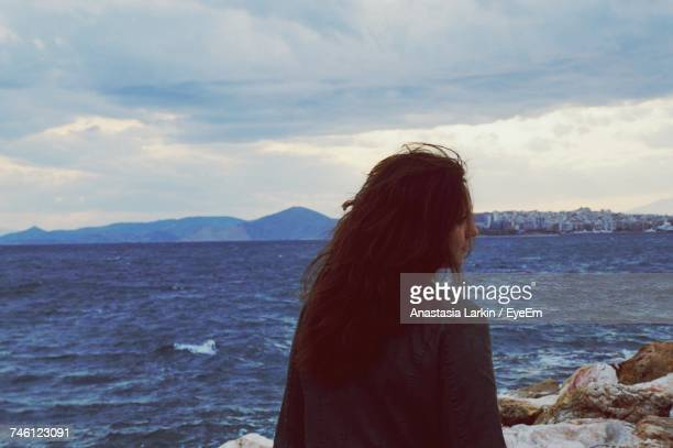 Rear View Of Woman By Sea Against Cloudy Sky