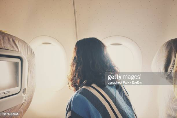 Rear View Of Woman By Window In Airplane