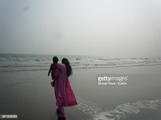Rear View Of Woman Carrying Baby Girl On Shore At Beach Against Sky