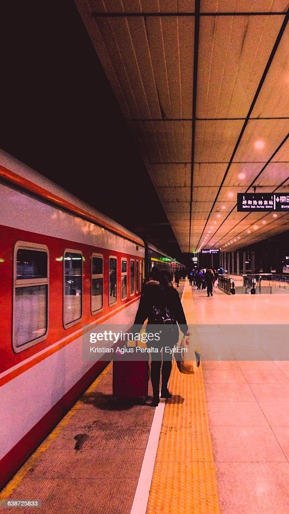 Rear View Of Woman Carrying Luggage On Railroad Station Platform At Night