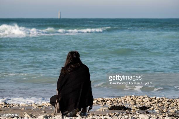 Rear View Of Woman Crouching On Shore At Beach Against Sky