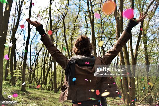 Rear View Of Woman Enjoying With Confetti On Woodland