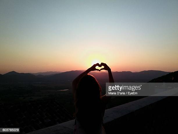 Rear View Of Woman Forming Heart Shape With Hands While Standing By Retaining Wall During Sunset