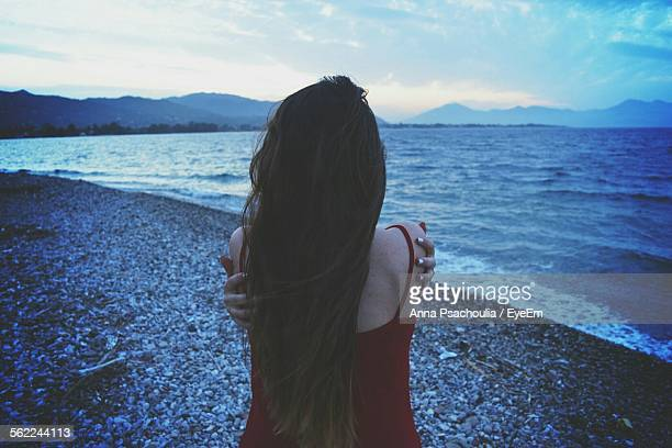 Rear View Of Woman Giving Herself Hug On Beach At Dusk