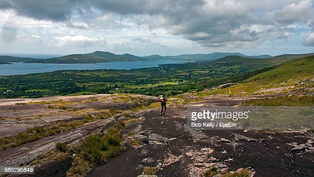 Rear View Of Woman Hiking On Rocky Landscape Against Sky At Beara Peninsula