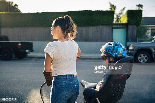 Rear view of woman holding bicycle with son sitting on back seat outdoors