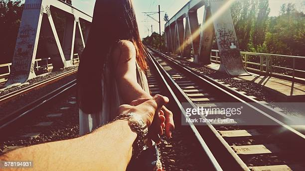 Rear View Of Woman Holding Mans Hands While Walking On Railroad Bridge