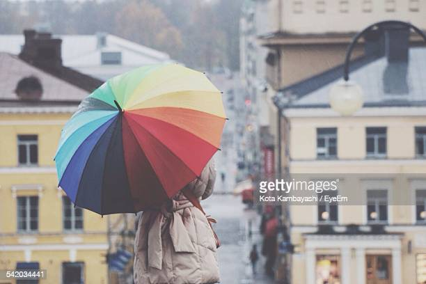 Rear View Of Woman Holding Multi Colored Umbrella Against Buildings