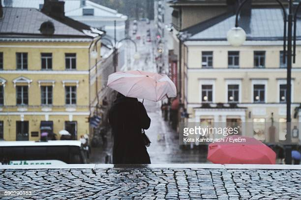 Rear View Of Woman Holding Umbrella On Steps During Rainy Season