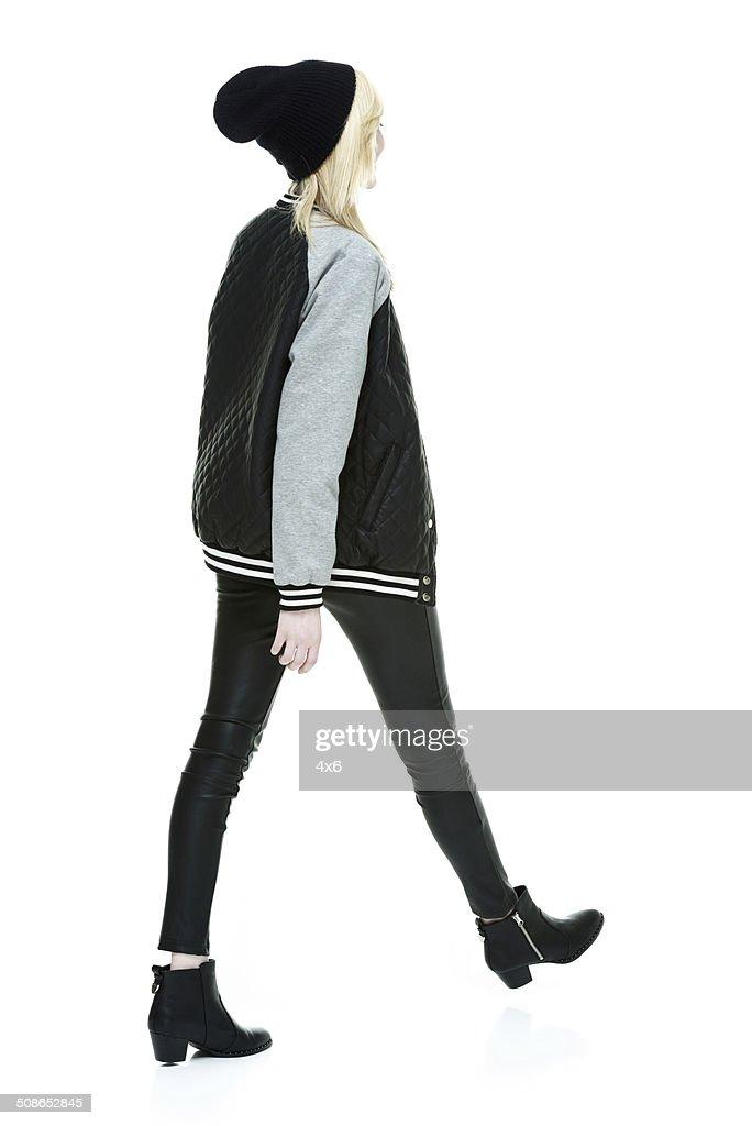 Rear view of woman in jacket & walking : Stock Photo