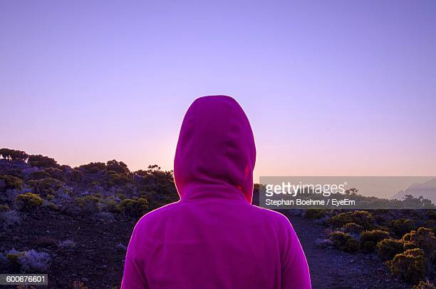 Rear View Of Woman In Pink Hooded Shirt Against Clear Sky During Sunset