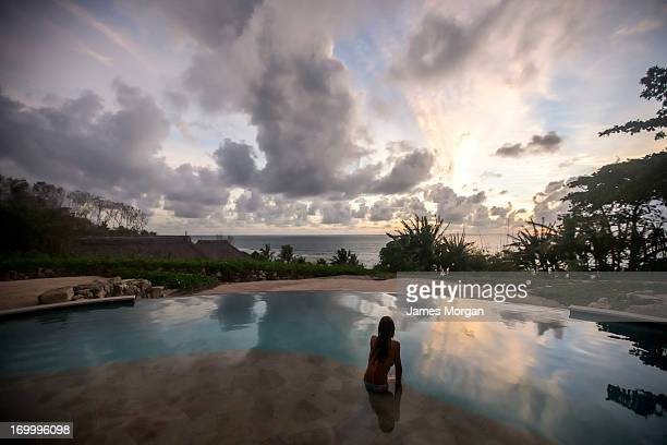 Rear view of woman in pool with sunset reflection